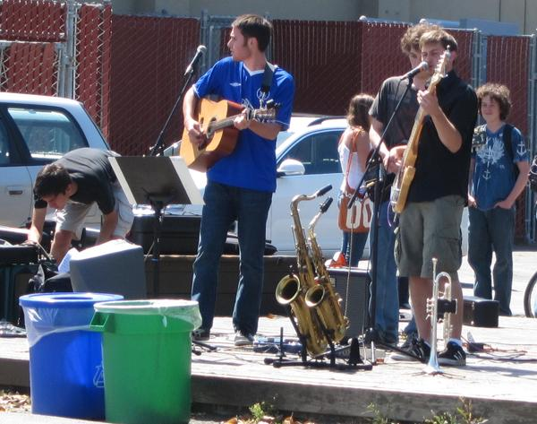 Members of Late Notice, a jazz band, quietly set up their equipment as members of Furious George perform an alternative song.