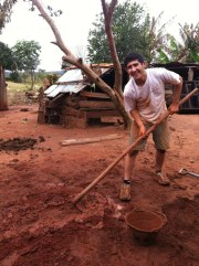 Noam digs holes to prepare for the stone stoves that his group is about to install.
