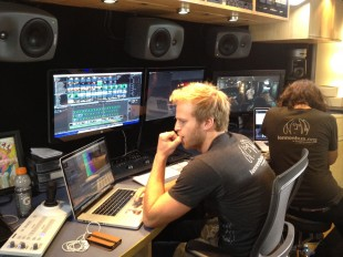 "Inside the John Lennon Educational Tour Bus, engineers are working on the production of Sequoia High School's music video for their original song, ""We are the Future (Now is the Time)."" [Photo by Addie McNamara]"