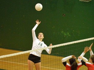 Outside hitter Becca Raffel rises above the net for a hit in Paly's straight-set victory over crosstown rival Gunn High School.  Photo by Matt Ersted.