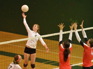 Shelby Knowles tips the ball over the net and two Gunn High School blockers in Paly's straight-set victory over its crosstown rival.  Photo by Matt Ersted.