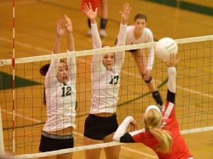 Jade Schoenberger (12) and Bella Graves (17) rise above the net to block a spike from a Gunn High School hitter in the crosstown matchup between Paly and the Titans Tuesday night.  Photo by Matt Ersted.