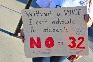 A demonstator holds up a sign advocating for No on 32 at the Palo Alto Caltrain station yesterday. Photo by Cathy Rong.