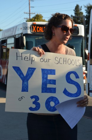 Paly teacher Rachael Kaci holds up a sign urging for people to vote Yes on Prop 30 at the demonstration yesterday. Photo by Cathy Rong.