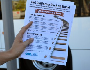 Demonstrators handed out flyers at the Caltrain station, for Yes on Prop 30 and 32. Photo by Cathy Rong.
