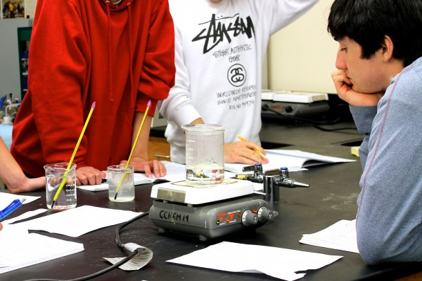 Chemistry students gather around a beaker during an in-class lab.   Photo by Levi Schoeben.