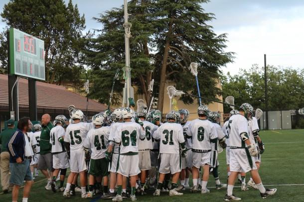 The Paly varsity boys lacrosse team meets in a huddle before the game. Photo by Parker Devine.
