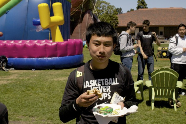 Junior William Yang enjoys one of the burgers paid for by the Associated Student Body and served by the Parent Student Teacher Association.