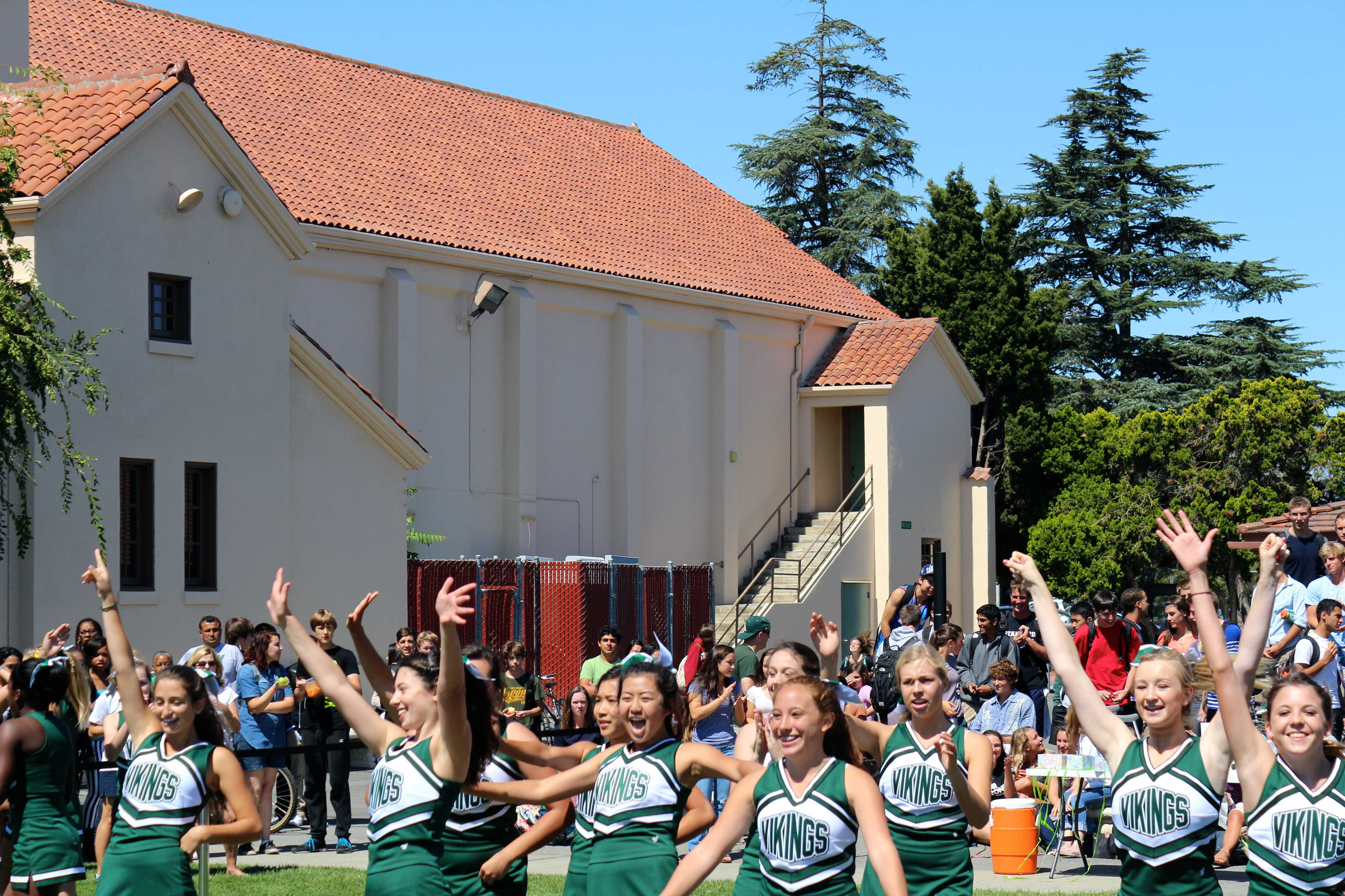 Cheerleaders wave to the gathered students. Photo by Frankie Comey