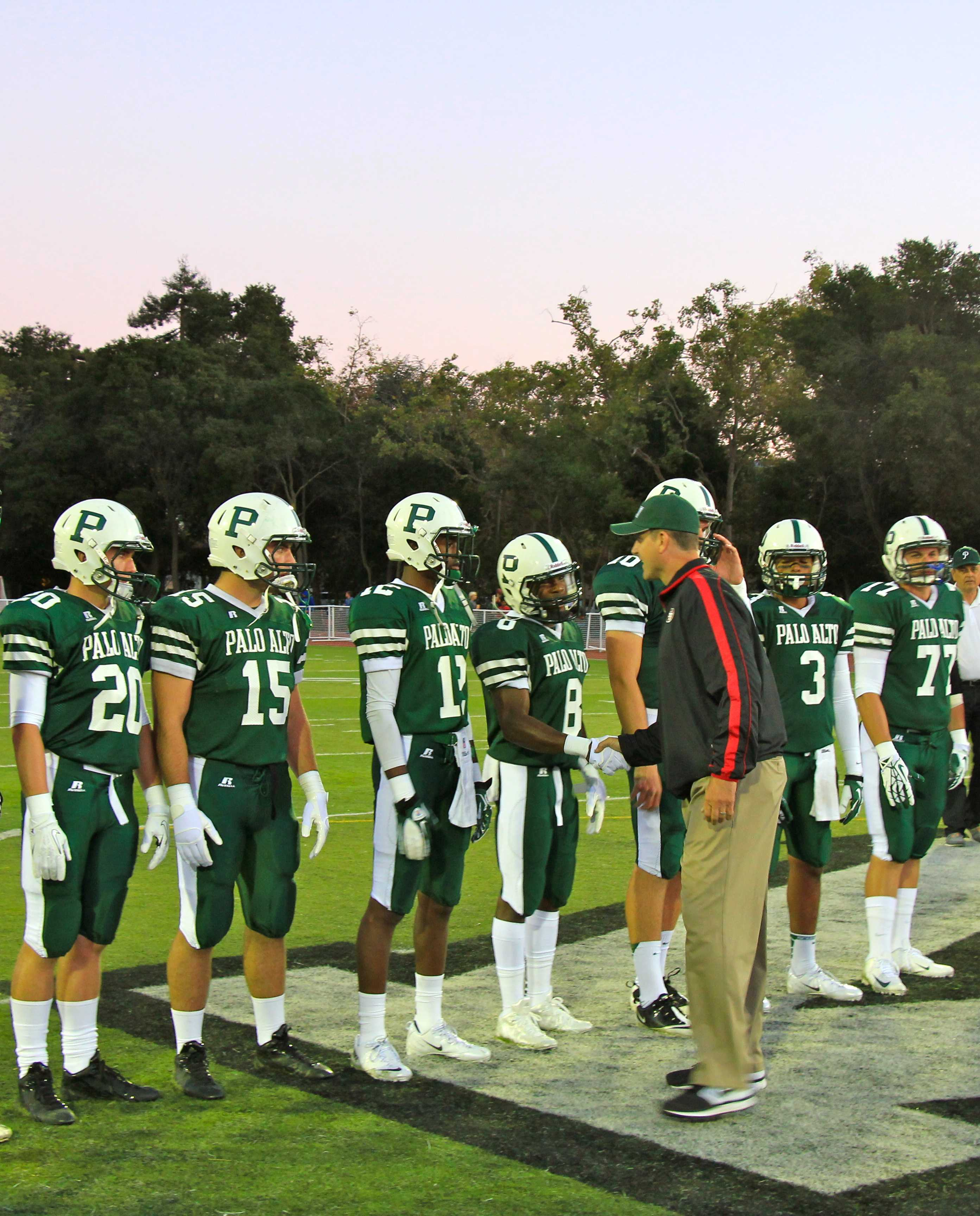 Harbaugh shakes hands with the Viking football captains. Photo by Scott Andrews