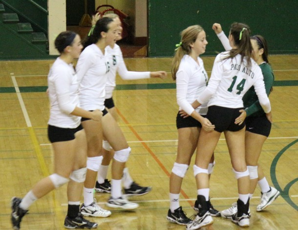 Becca Raffel (14) celebrates with her teammates after winning a hard-fought rally against Castilleja. The Vikings swept the Gators in three sets. Photo by Liana Pickrell.
