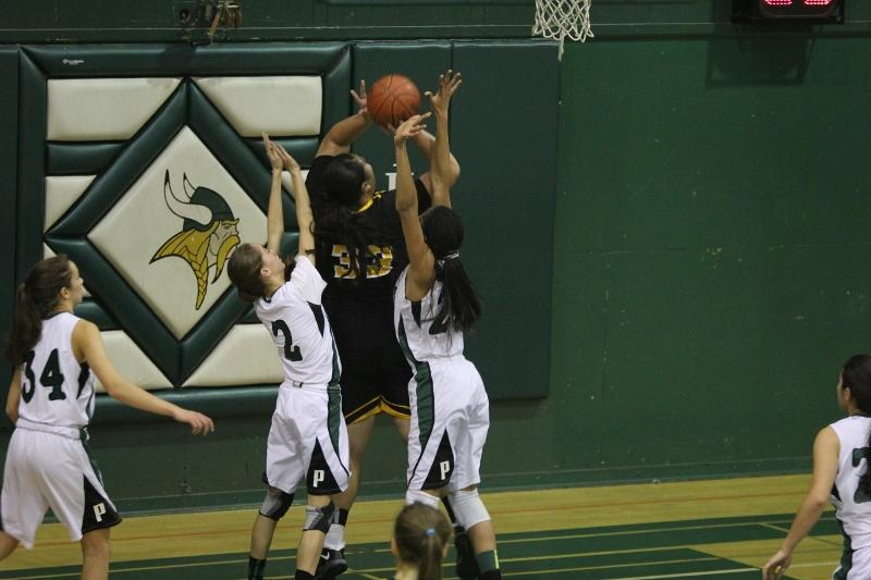 Freshman Jacky Moore and sophomore Alexis Harris attempt to block Joeseta Fatuesi's shot. Photo by Maddy Jones.