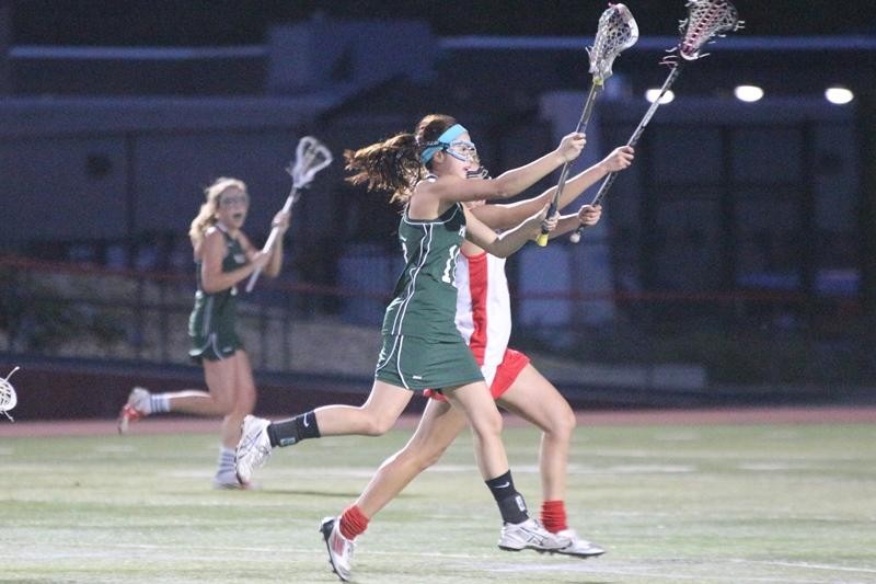 Junior attacker Claire Chevallier passes the ball across the field while under pressure from a Gunn defender. Chevallier controlled one draw. Photo by Maddy Jones.