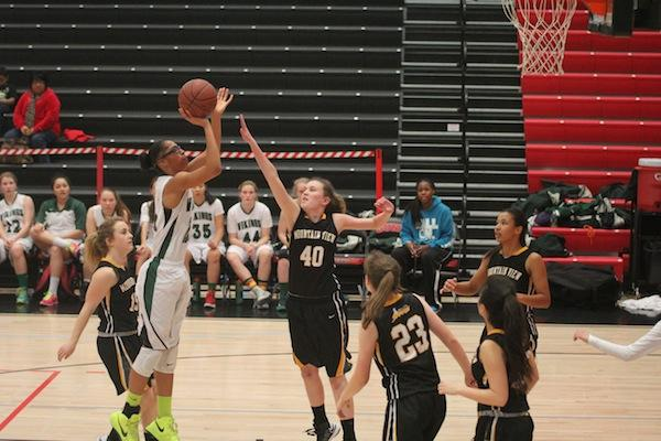 Sophomore Alexis Harris shoots over a Spartan defender. Harris scored 11 points. Photo by Liana Pickrell.