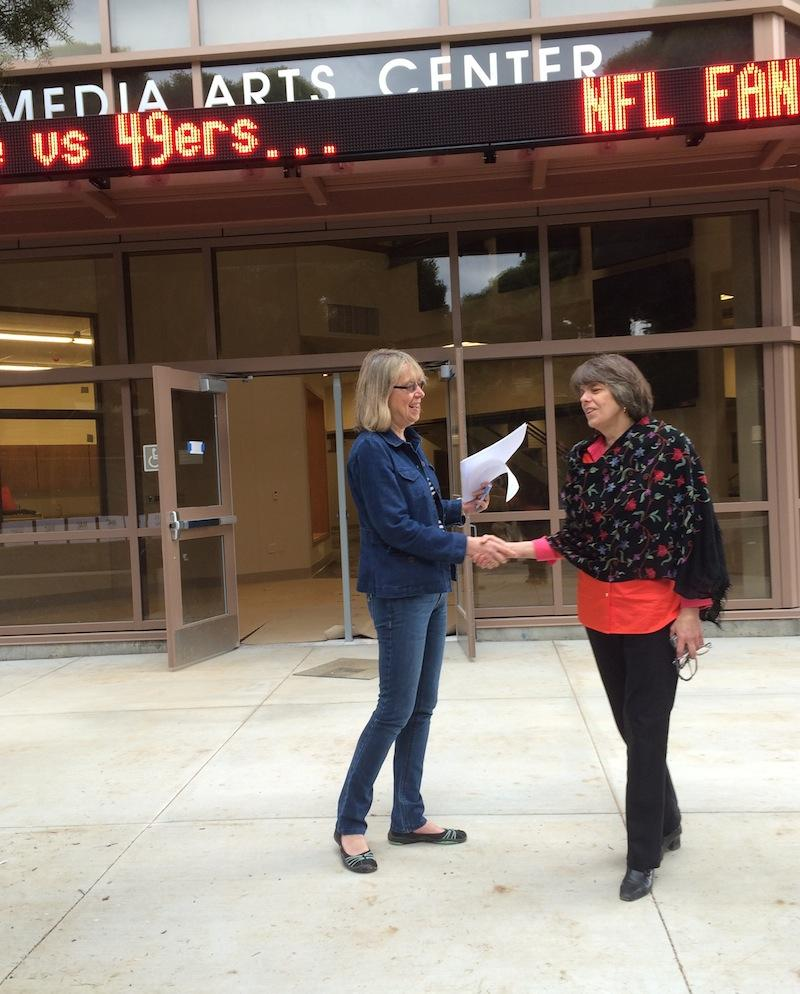 The Campanile adviser Esther Wojcicki and free-speech icon Mary Beth Tinker shake hands at a press conference during lunch today in front of the Palo Alto High School Media Arts Center, which is scheduled to open August 2014. The Brin-Wojcicki Foundation, established by Wojcicki's daughter Anne Wojcicki and her husband Sergey Brin, donated $81,500 to support the building. Tinker is on a Student Press Law Center-sponsored tour across the nation. Photo by Lizzie Chun.