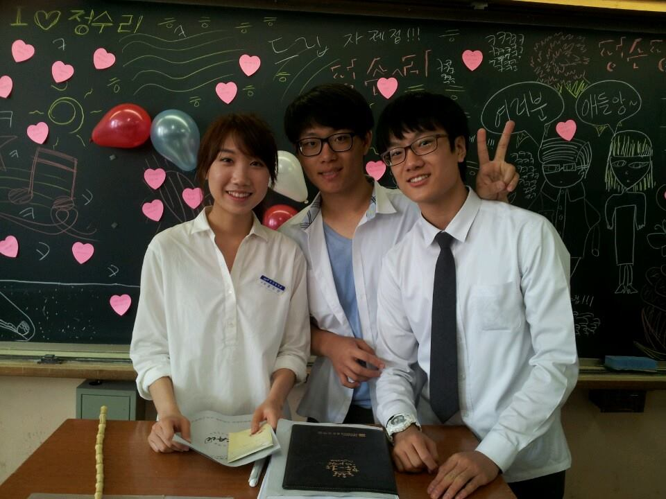Henry Do Hyun Kwon poses for a pictures with two of his classmates in South Korea.