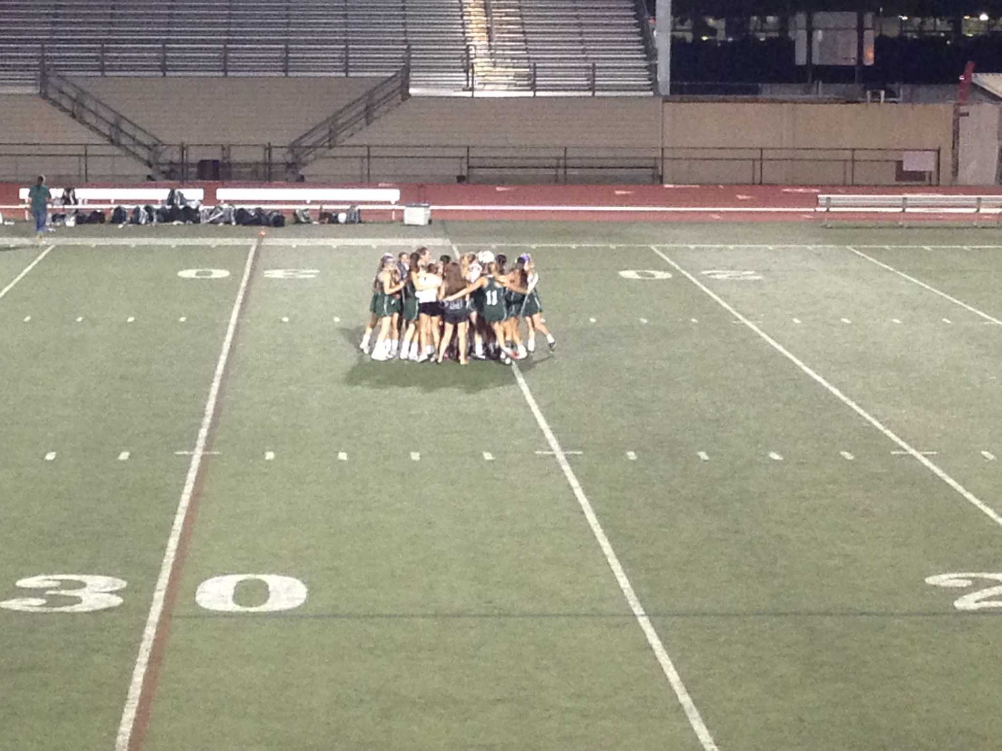 The Palo Alto girls' lacrosse team huddles after their win against St. Francis. Photo by Molly Fogarty.