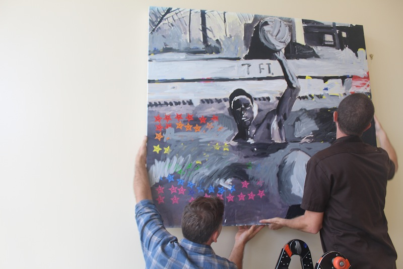 Two helpers hang up Franco's painting of a water polo player in 1993. Over 10 of Franco's paintings that are inspired from yearbook photos are spread throughout the Media Arts center. Photo by Adele Bloch.