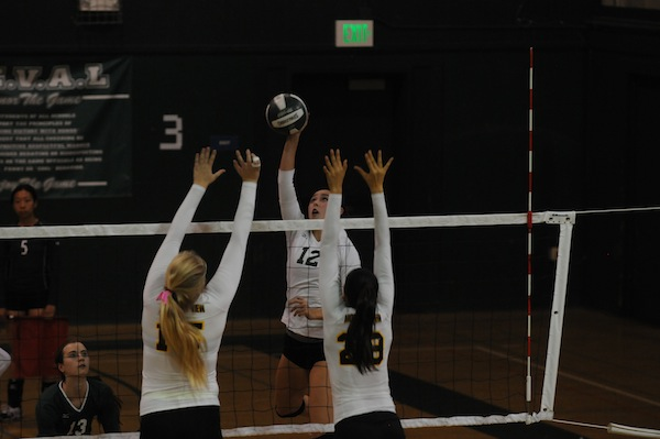 Senior captain and outside hitter Jade Schoenberger spikes the ball past two Spartans. Schoenberger had kills in two of the sets. Photo by Liana Pickrell.