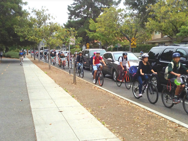 "Due to the Caltrain crossing and traffic light, a large group of students will often aggregate in front of the Churchill and Castilleja intersection.""The second that a train passes by, all of the bikers rush towards the school entrance and block off a good portion of the road,"" according to Palo Alto High School junior Spencer Yu. Photo by William Zhou."