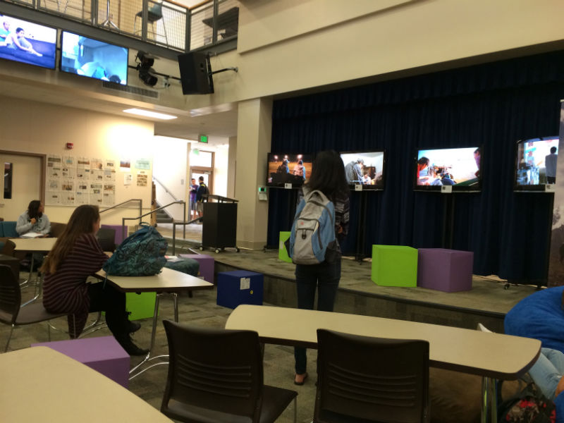 Students watch Global Lives videos after school in the MAC. The video exhibit, which will be running Oct. 13-18, features footage of ordinary people from 17 different countries. Photo by Jeanette Wong.