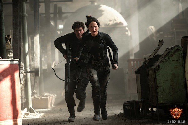 Katniss (Jennifer Lawrence) and Gale (Liam Hemsworth) sprint to escape falling rubble while visiting District 8. Photo courtesy of Lionsgate Entertainment.