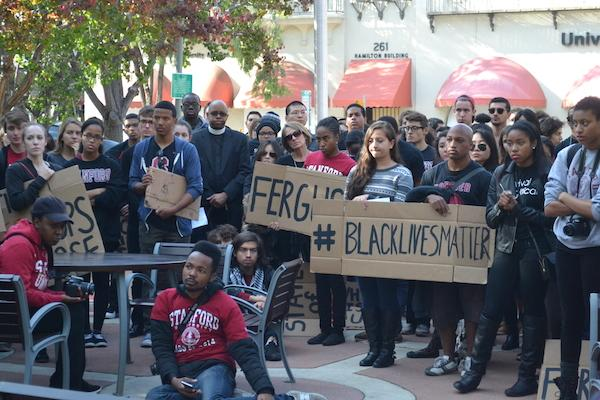 """Protesters carry signs saying """"Ferguson"""" and """"#blacklivesmatter"""" in front of Palo Alto City Hall. Photo by Amy Leung."""