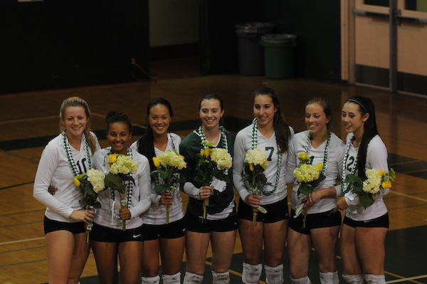 The seven graduating Paly seniors smile with their flowers and beads courtesy of other members of their team. Photo by Liana Pickrell.