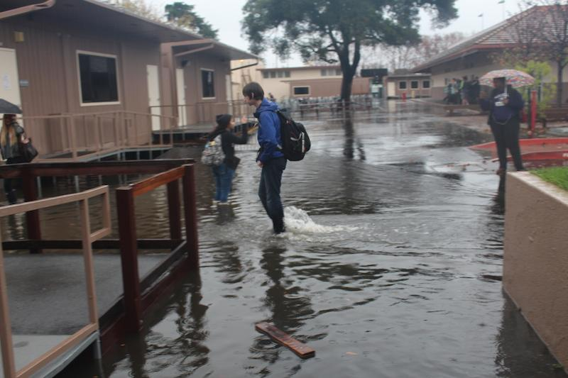 A student walks through the flooded area of the campus near the Student Center. Flooding in some areas of the campus reached over one foot deep today. Photo by Molly Fogarty.