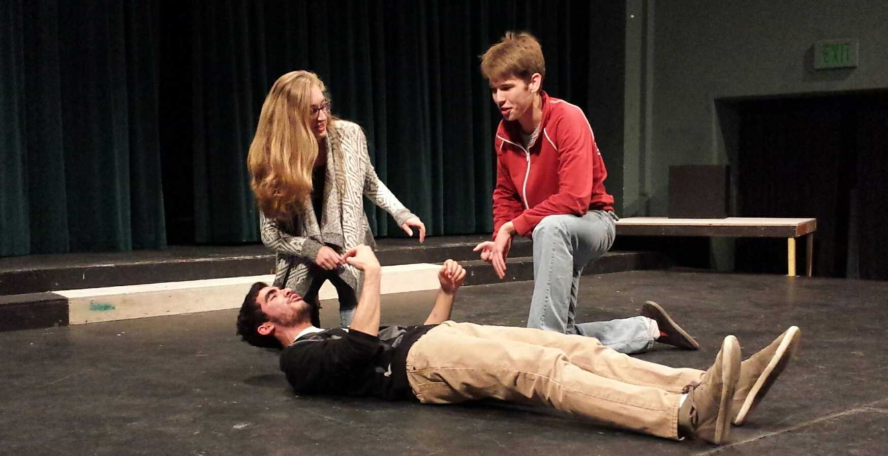 "Sophomores Andrea O'Riordan and Joey Kellison-Linn attempt to revive junior Paul Bleich in an improv game called ""Countdown,"" as practice for the upcoming competition on Friday. O'Riordan and Kellison-Linn will be among the six troupe members competing. Photo by Hannah Nguyen."