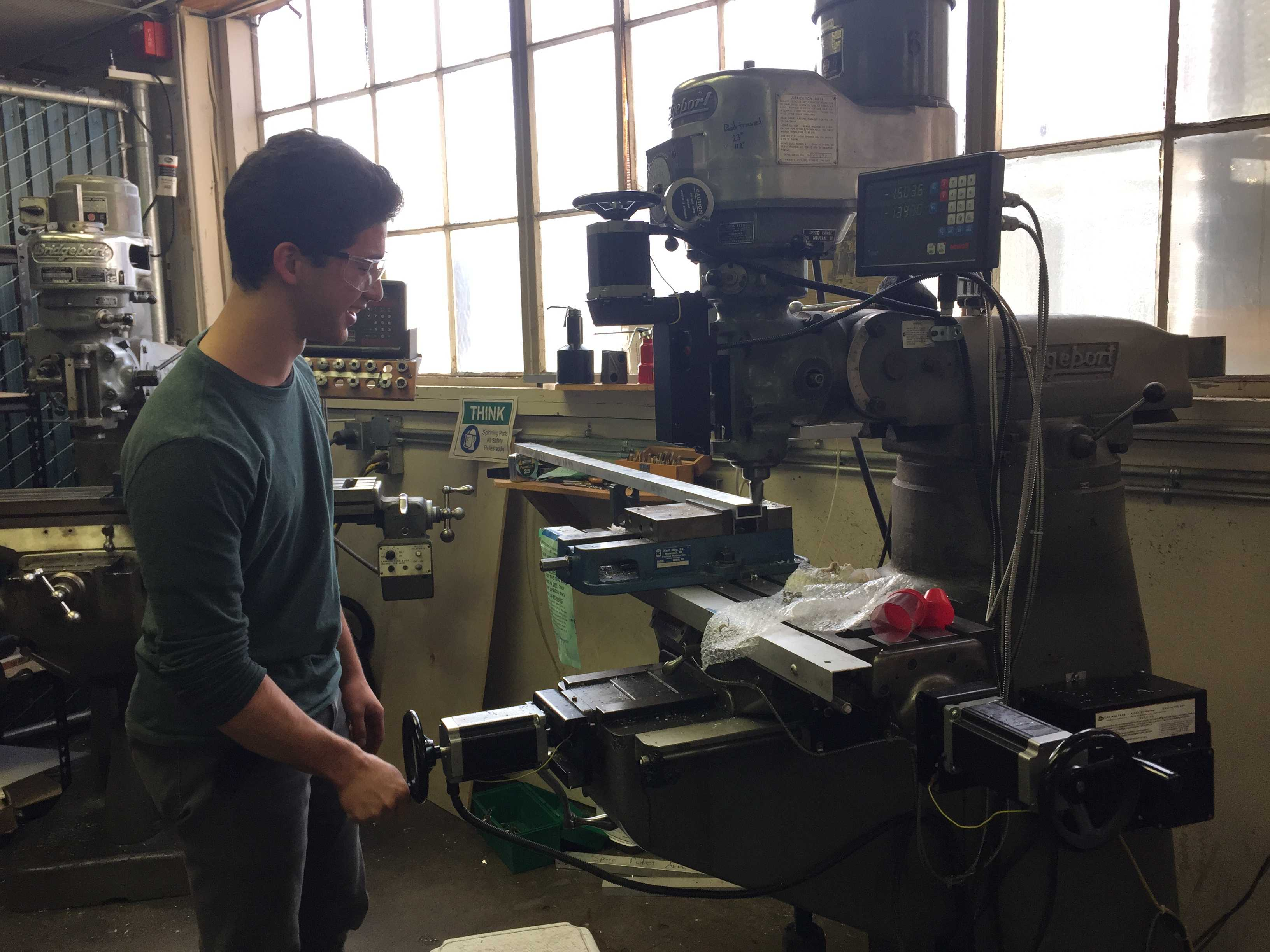 Senior Osamu Yasui uses a metal cutter to prepare parts for the robot. Photo by Dhara Yu.