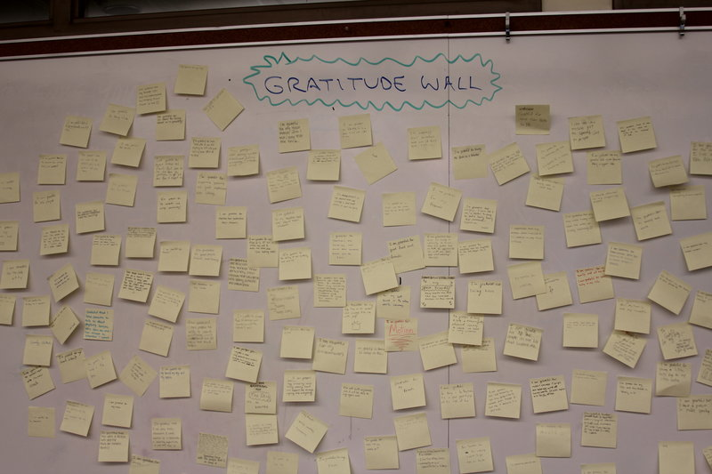 "The ""Gratitude Wall"" in the classroom of AP Economics teacher Eric Bloom features sticky notes of things that Paly students are grateful for. Several Paly teachers invited students to participate in this activity on Monday after the school was informed of the death of a Gunn senior this past weekend. Photo by George Lu."