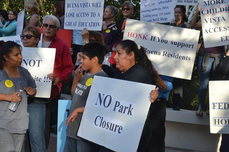 A woman and boy hold signs alongside about 50 others to protest the closure of Buena Vista Mobile Homes in front of Palo Alto City Hall. Photo by Amy Leung.