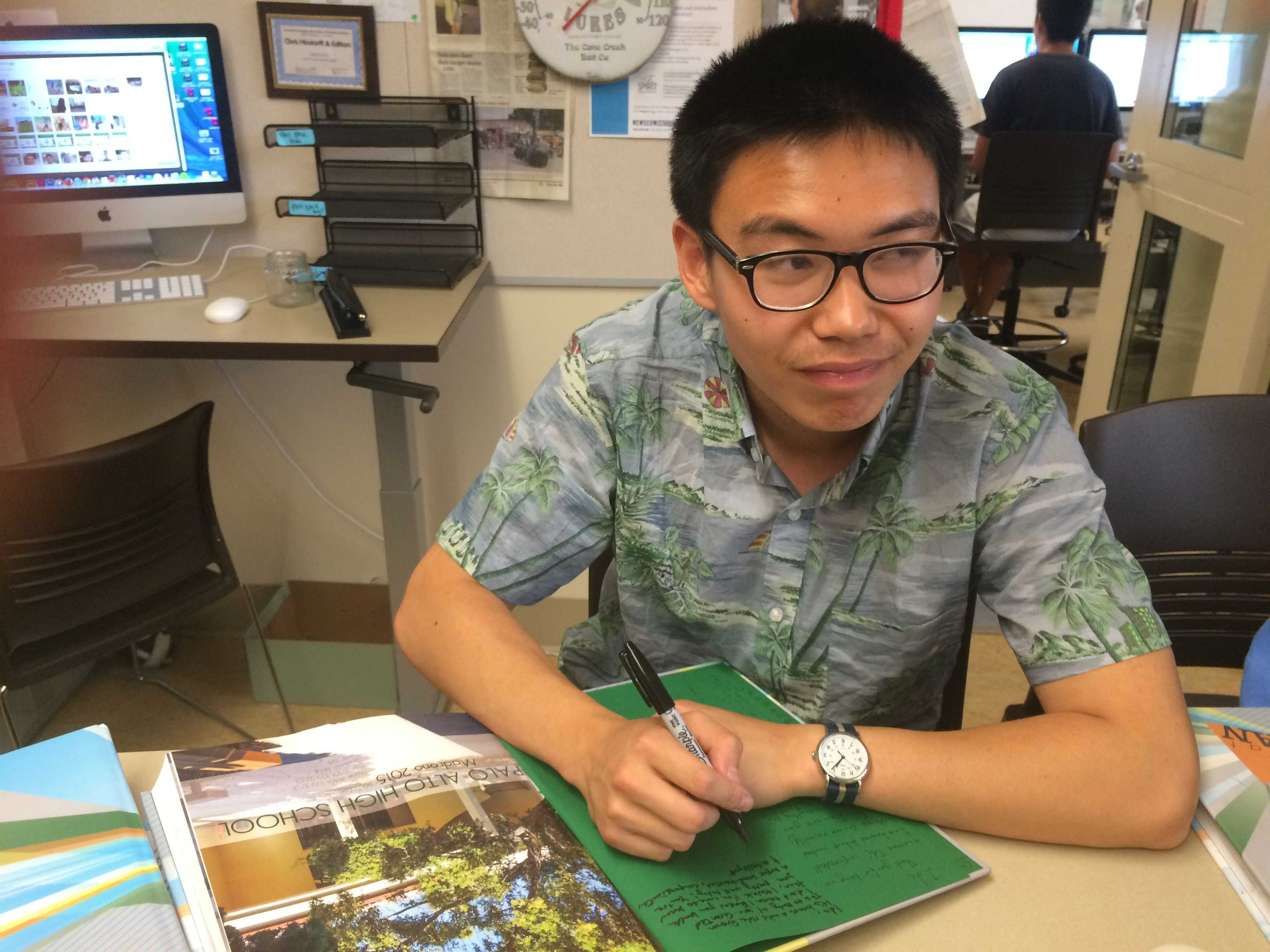 Senior staff writer Charles Yu ponders what to write in a yearbook. Photo by Emma Chiu.