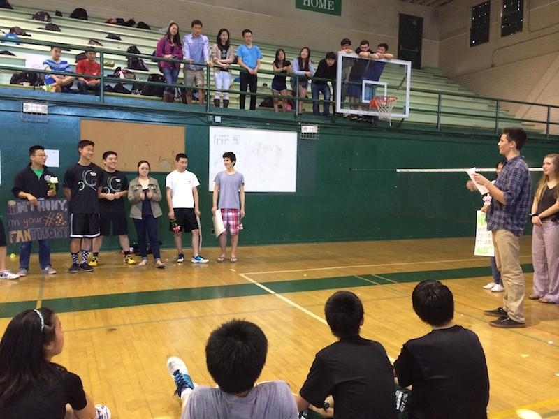 Sophomore Josh Code speaks about Senior Alec Deng on Palo Alto High School's senior badminton night. Before an eventual 18-12 victory versus Lynbrook, the team gathers around to hear the speech. Photo by Jeanette Wong.