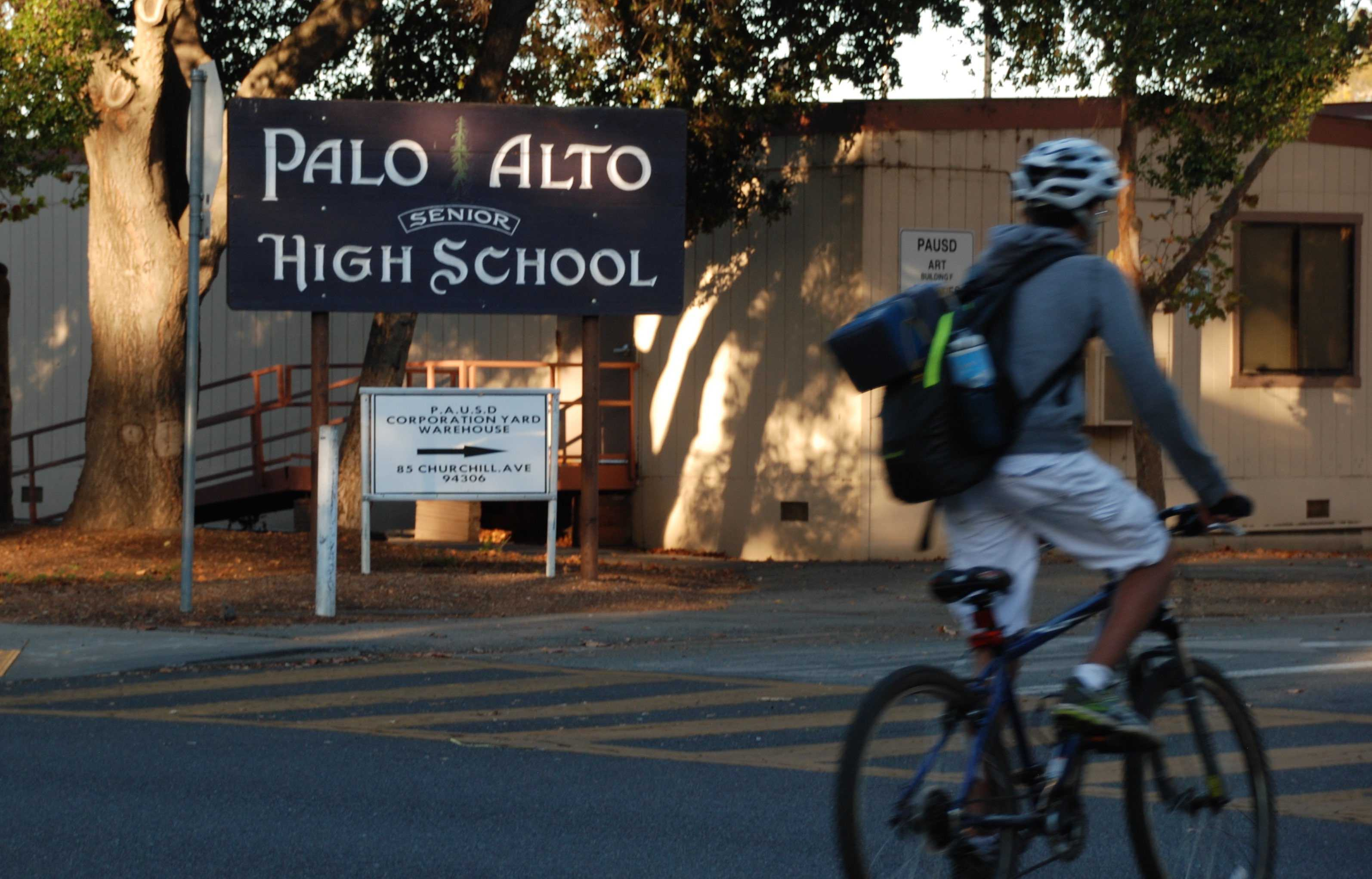 "A Palo Alto High School student bikes past the Paly sign located at the intersection of Churchill Avenue and Castilleja Avenue before school. The school sign, one that does not have legal trademark according to Assistant Principal Jerry Berkson, was featured on a flyer .. ""I think what he [the organizer of the event] did was deceptive in nature and I didn't like it,"" Assistant Principal Vicki Kim said. Photo by Jeanette Wong."