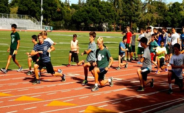 The Palo Alto High School boys' cross country team warms up during practice at the Paly track. After finishing third