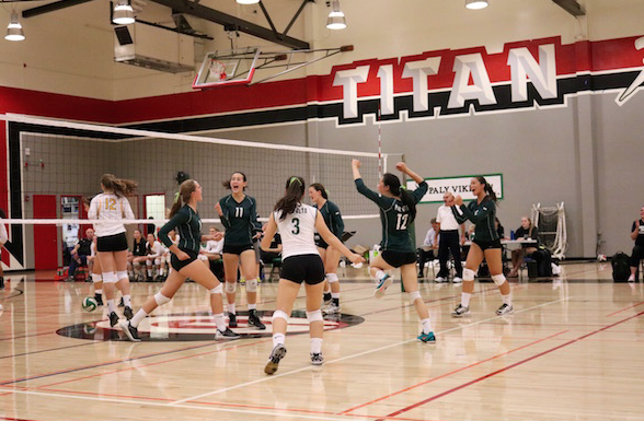 The Palo Alto High School girls' volleyball team celebrates after Senior middle blocker Claire Krugler gets a block against Mountain View High School. Photo by Victor Carlsson.