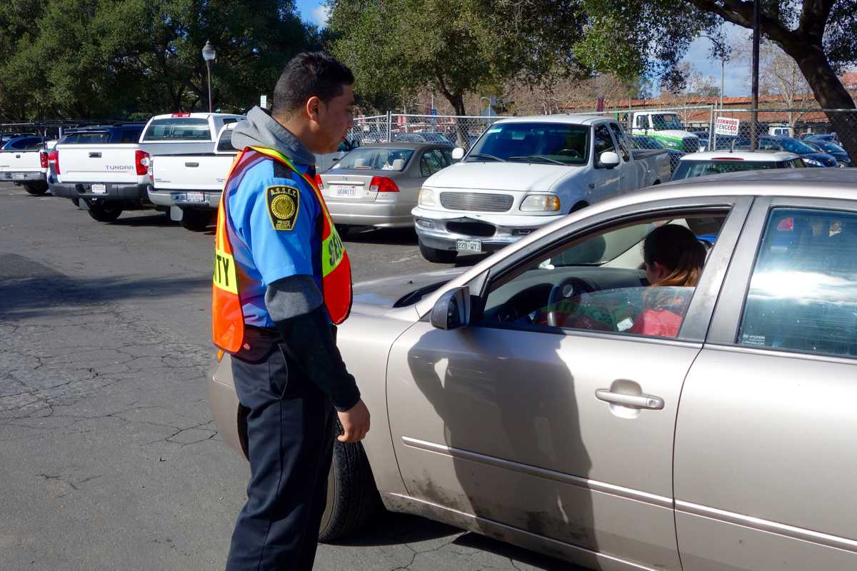 A hired security officer examines a student's parking permit. The Paly administration has upped security measures in light of Super Bowl 50 traffic.