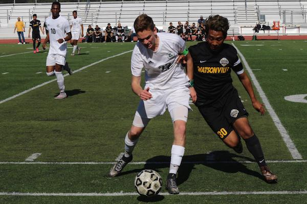 """Senior captain and outside midfielder Cole Tierney pushes off a Watsonville High School defender during the second half of the Central Coast Section playoff quarterfinal match on Saturday at the Palo Alto High School Viking Stadium. The score of the game did not reflect the Vikings' effort, according to senior outside midfielder Dami Bolarinwa. """"I think we played a lot better than the score could ever say about us,"""" Bolarinwa said. Photo by Emma van der Veen."""