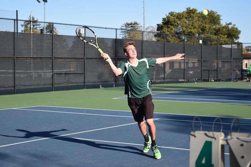 Junior Adrian Smith swings back his racket to return the ball in a doubles match against Cupertino on Thursday at Paly. Photo by Sam Lee.