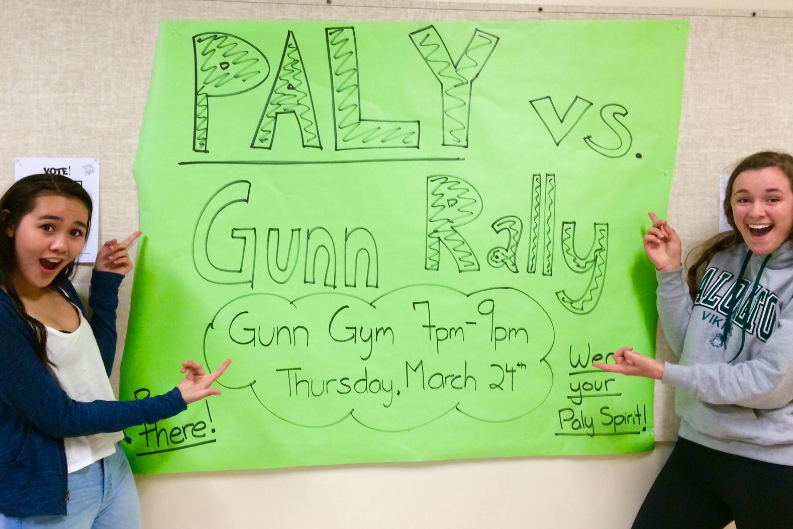 Juniors Kaitlyn Vi and Nora Danie stand in front of the promotional poster for the upcoming night rally.