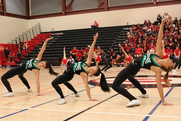 Paly dance team members (left to right) junior Nathalia Castillo, senior Melanie Guan and senior Emma Sternfield perform in a collaboration between the Paly and Gunn dance teams at the first ever Paly vs. Gunn night rally on Thursday at Gunn. Photo by Emma van der Veen.