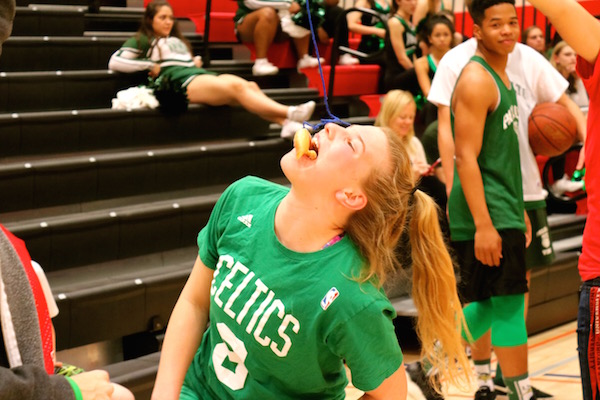 Junior Skylar Burris attempts to eat a donut in the obstacle course competition as part of the Paly upperclassmen team. Photo by Emma van der Veen.