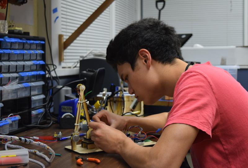Senior Nathan Kau works on his robotic arm in preparation for the Santa Clara County regional tournament for Science Olympiad this weekend. The Palo Alto High School Science Olympiad team needs to place in the top four in order to advance to the state competition. Photo by Chirag Akella.