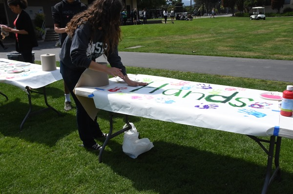 Senior ASB Treasurer Courtney Hall places a handprint onto the 'These Hands Don't Harm' poster set up in the Quad during lunch on Wednesday for Sexual Assault Awareness Day during Not In Our Schools Week 2015. This year, the focus will be on the positive aspects instead. Photo by Liana Pickrell.