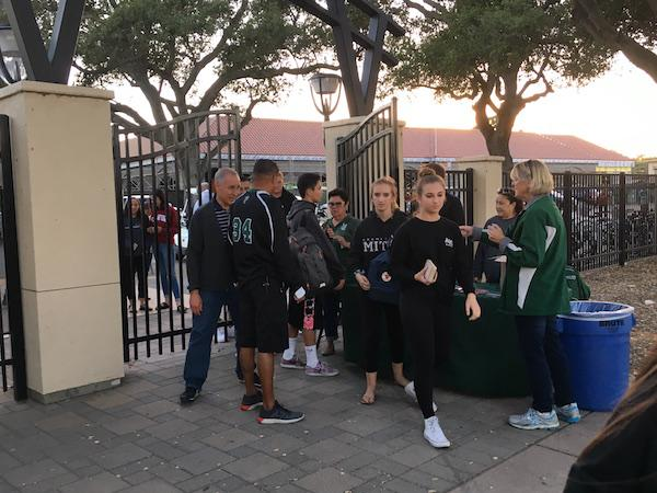 Palo Alto High School students wait in line to enter tonight's home football game against Archbishop Mitty High School. Assistant principal Jerry Bergson says that the procedure was implemented to help keep football games safe.