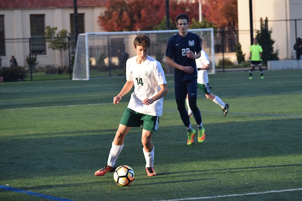 Sophomore outside midfielder Jason Shorin dribbles up the sideline. Shorin is a first-year Varisty player on the boys' soccer team. Photo: Emma van der Veen.