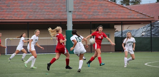 Senior midfielder and captain Natalie Maloney attempts to make a pass to freshman forward Sophie Vogel, who makes a cut towards the goal. Maloney would go on to score four goals for Palo Alto High School, in its 11-0 rout of El Camino High School on Thursday at home. Photo: Sam Lee.