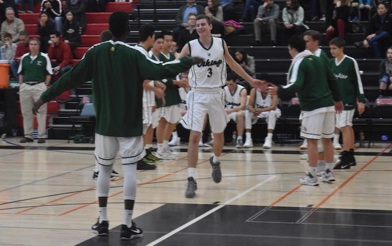 Junior guard Spencer Rojahn gets pumped up by fellow junior guard Brey Johnson pregame. Rojahn hit two early three-pointers on Friday against Gunn High School. Photo: Rachel Code